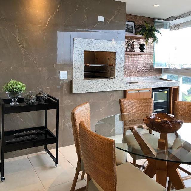 Área gourmet com churrasqueira revestida de porcelanato marmorizado, mesa redonda de vidro com cadeiras bege e piso branco.