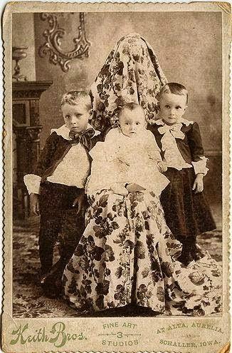 Foto de três crianças com a mãe escondida por um longo pano