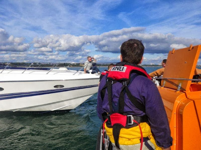 Poole lifeboat crew discussing the tow with the skipper of the  18.3m motorcruiser with engine failure 6 October 2013 Photo: RNLI Poole/Anne Millman