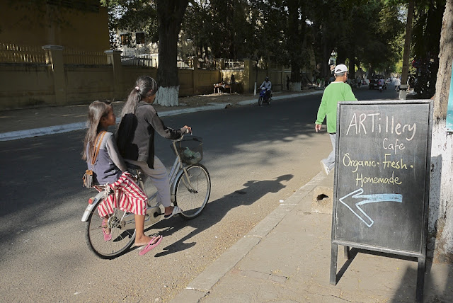 "two girls riding a bicycle by a sign which reads ""ARTillery Cafe. Organic. Fresh. Homemade."""