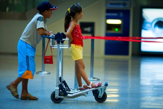 Two children playing with a luggage cart in the airport. Rome Italy