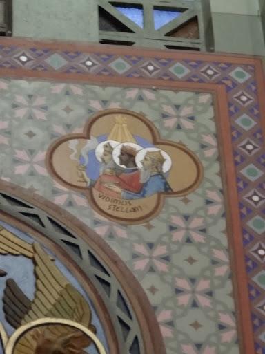 """""""Vidimus Stellan"""" que em português significa """"Vimos a Estrela de Belém"""". A figura simboliza os Santos Reis (Melchior, Baltazar e Gaspar) representando a humanidade na chegada do Rei. As oferendas de ouro, incenso e mirra vem simbolizadas no cofre, turibulo e redoma de perfume. Verifica-se acima a Estrela de Belém."""