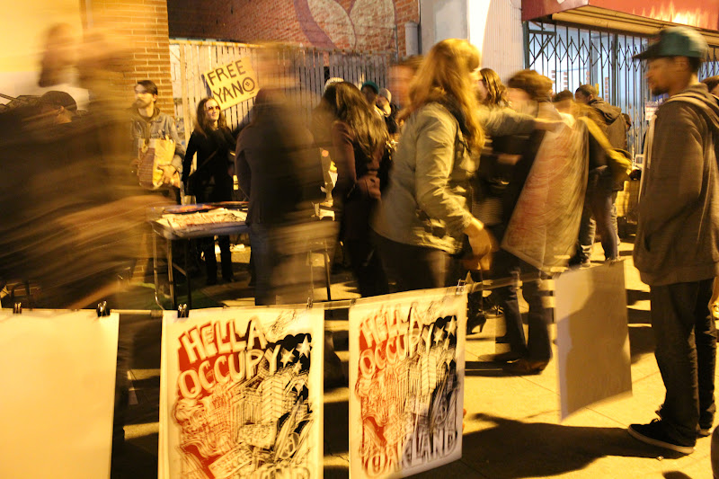 """Photo: """"Hella Occupy Oakland"""" posters being silk screened on the sidewalk and hanging to dry between light posts on Telegraph Ave."""