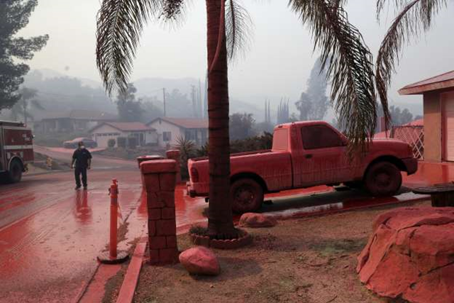 A truck and a street are covered in red fire retardant dropped by an air tanker as crews battle a wildfire on 10 August 2018 in Lake Elsinore, California. Photo: Marcio Jose Sanchez / AP Photo