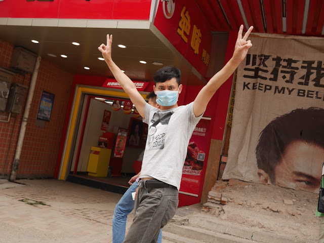 young man wearing a face mask with his hands in the air and fingers making V signs.
