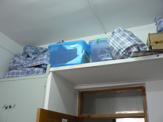 items stored on a shelve above a doorway in a dorm room at Dalian Maritime University in China