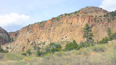 The pink rock of the canyon wall here in the Frijoles Canyon of Bandelier National Monument may look like sandstone, but it is actually volcanic ash that compacted over time into a soft crumbly rock called Tuff. Tuff is very easily eroded wind and rain, with some components of the tuff eroding more easily than others so that over time the exposed rock takes on a Swiss Cheese appearance.