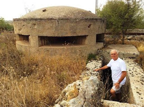 Mike Stanko stepping down into the underground entrance of an old bunker just off a Sicily beach