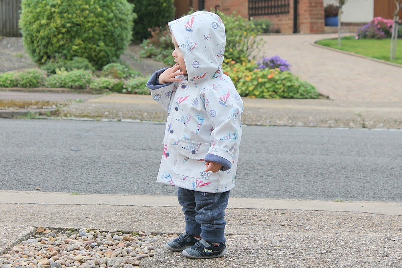baby-wearing-raincoat-looking-at-road