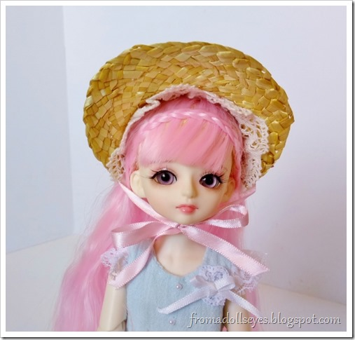 A small bjd with pink hair (Yuna) wear a half bonnet.  It looks so cute on her.