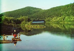 Женщина сидит в тихом местечке на реке Сим, которая является частью бассейна реки Волга, 1910 год