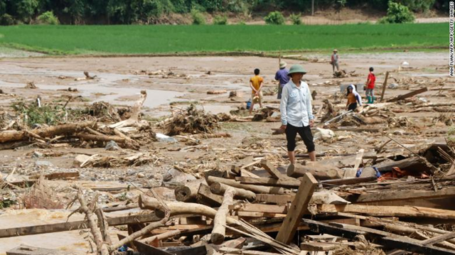 Residents clear debris in a village damaged by flash flooding in Vietnam's Yen Bai province on Saturday, 21 July 2018. Photo: Anh Tuan / AFP / Getty Images
