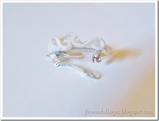 A close up of the side of the doll sized hair clip showing off the small barrette used as a base.