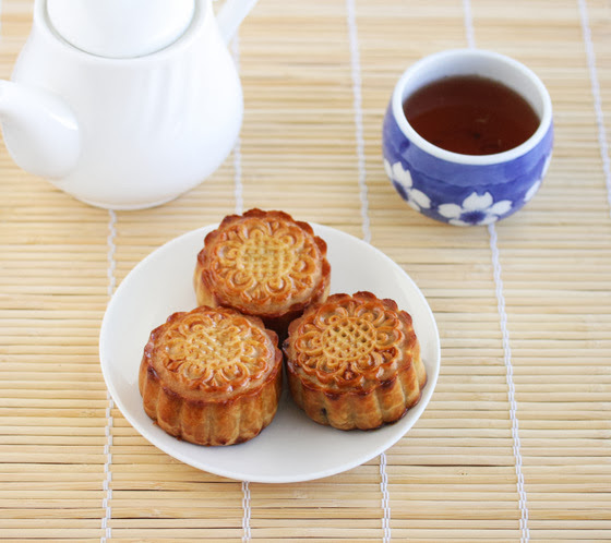 photo of three traditional mooncakes on a white plate with tea on the side