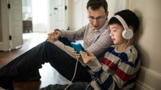 man and young boy sit and look at tablet together