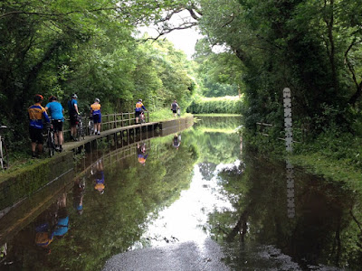 Cyclists walking on path above flood