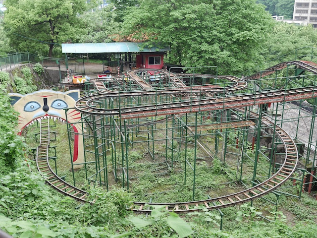 metal roller coaster with track going through a giant cats mouth