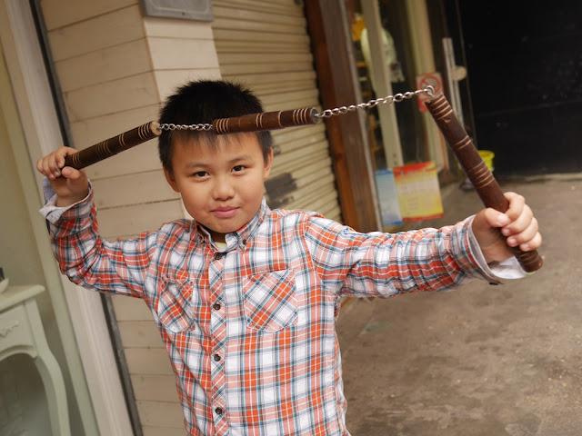 boy posing with a sanjiegun (three-sectional staff) in Changsha, Hunan