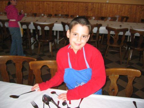 Jonas legt het bestek klaar op de tafels.