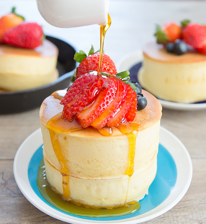 a photo showing syrup being poured over a stack of Japanese-style pancakes garnishes with fresh strawberries