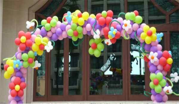 Arco de globos con flores como entrada para una fiesta de niños