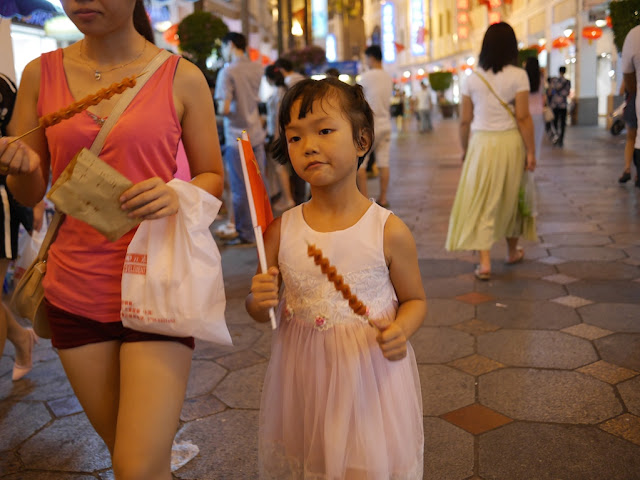 young girl holding a meat kebab and a PRC flag in Zhongshan, China