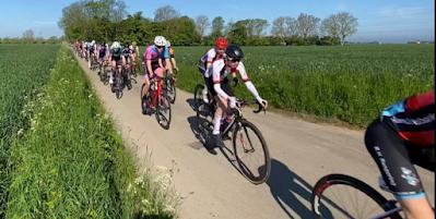 Klunga av cyklister på smal väg mellan två gröna ängsfält.
