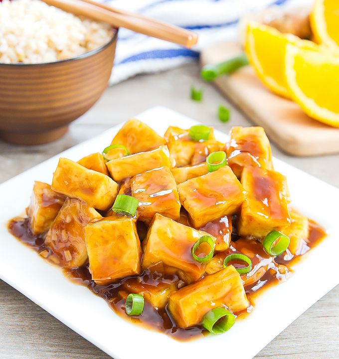 a plate of crispy baked orange tofu with a bowl of rice in the background