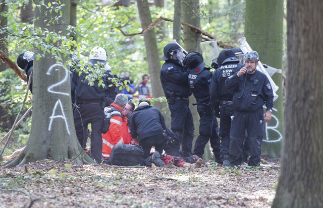 A man receives medical treatment after he fell off a tree at the Hambach forest in Kerpen, Germany, Wednesday, 19 September 2018. Activists are protesting against the expansion of a coal strip mine in western Germany that would entail the chopping down of an ancient forest. Photo: Christophe Gateau / dpa / AP