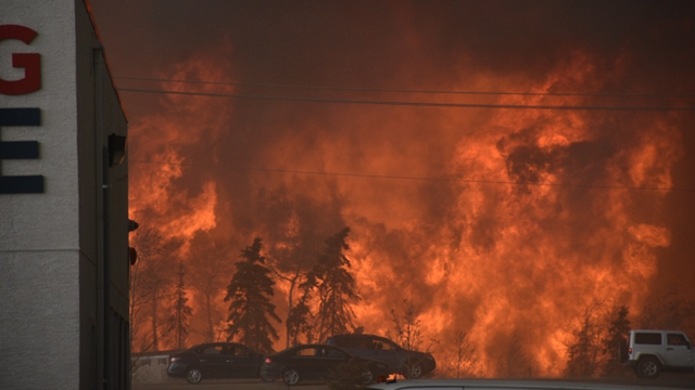 Flames are seen from the Sawridge Motel in Fort McMurray, Alberta, on 3 May 2016. The entire city of 60,000 was ordered evacuated. Photo: Terry Reith / CBC