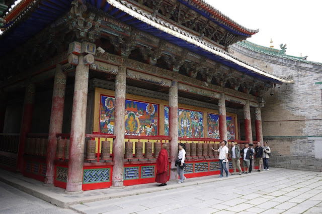 Tibetan monk and tourists turning prayer wheels at Kumbum Monastery (Taer Si) in Qinghai, China