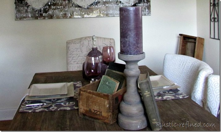 Purple candlestick, antique books and boxes set a pretty summer table