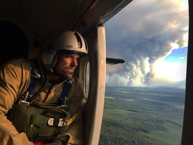 A firefighter looks out of a helicopter flying near a forest fire in British Columbia, 12 August 2017. Photo: BC Wildfire Service‏