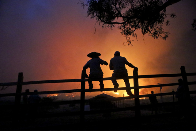 In this Sunday, 29 January 2017 photo, residents watch nearby wildfires in Portezuelo, Chile. Strong winds have continued to stoke the flames of the raging wildfires in Chile. Firefighters and residents fought the fast-spreading blazes on the ground on Tuesday, while a Russian supertanker plane and a Brazilian Hercules dumped thousands of gallons of water on the area. Photo: Esteban Felix / Associated Press