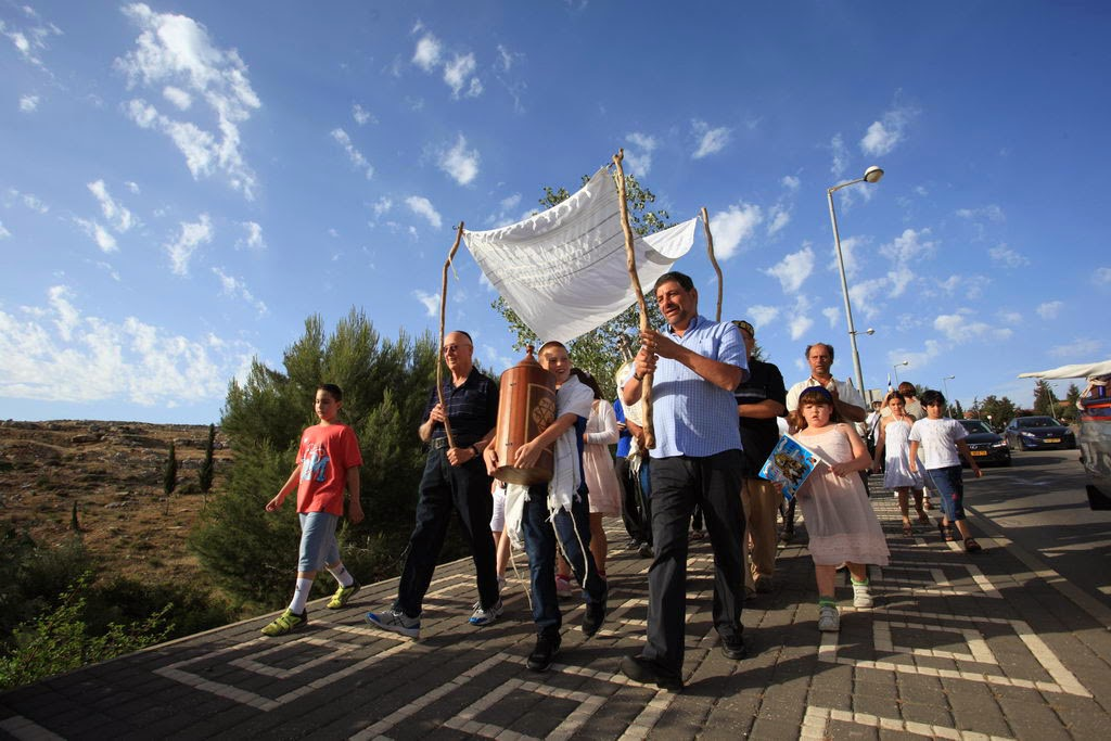 תהלוכת שמחה ברחובות הכפר עם ספרי התורה. Joyful procession through village streets with the scrolls.