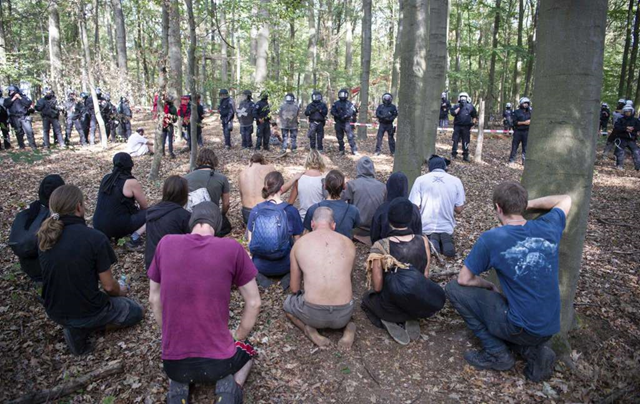 Activists kneel after a man fell off a tree house at the Hambach forest in Kerpen, Germany, Wednesday, 19 September 2018. People are protesting against the expansion of a coal strip mine in western Germany that would entail the chopping down of an ancient forest. Photo: Christophe Gateau / dpa / AP