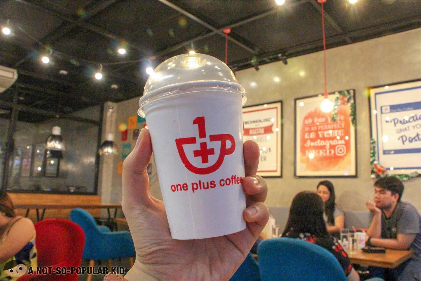 One Plus Coffee logo on a cup
