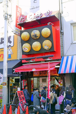 Sights of Osaka - Amerikamura and Takoyaki Stand Ganso Donaiya that I considered... and then I saw the balls on top rotated. And the lady taking orders is wearing a hat. And there are photos from articles and a Tripadvisor sticker on it. I also liked that this one they spotlight the cooking right in the front and side so you can watch your takoyaki being made fresh in front of you.