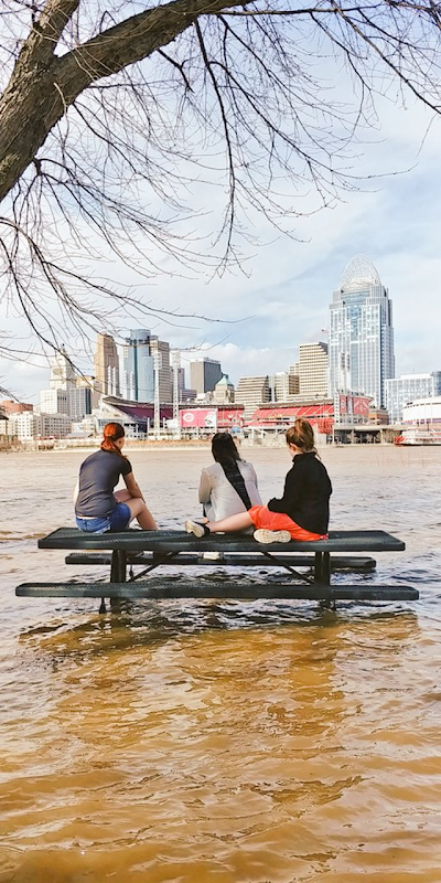 Three women sit on a partially submerged picnic table by the flooded Ohio River in Newport, Kentucky, 20 February 2018. Photo: Scott Ford / Twitter