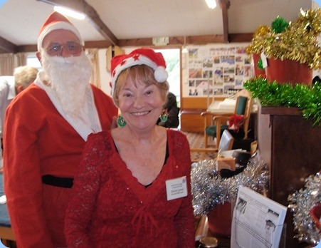 Santa Claus (Laurie Conder) and his helper (Diane Lyons) preparing the Christmas Raffle Hampers for the lucky winners of the raffle draw. Photo courtesy of Dennis Lyons.