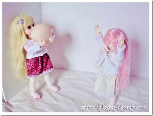 Two cute ball jointed dolls playing catch with a head.