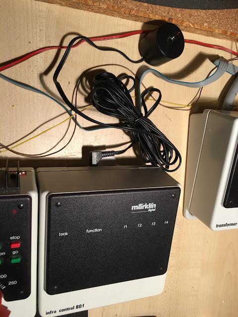 Unten die Infra control 80f mit hellgrauem Kasten und schwarzem Oberteil. Hinten ist ein langes Kabel mit dem Infrarot-Empfänger angeschlossen. Der sieht fast aus wie eine Filmdose mit trichterförmigem Loch. Nur etwas dicker und nicht so hoch. Auf der Infra Control liest man das märklin Logo, lock, function und f1, f2, f3, f4 für die Funktionen. Fertig.