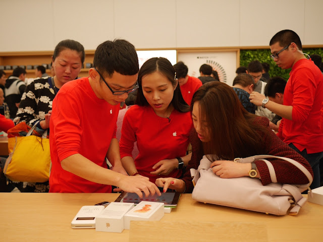 Apple employees assisting a customer