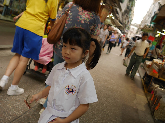 young girl walking on a pedestrian street in Macau's Three Lamps District