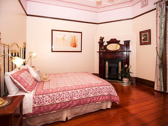 A very period bedroom, every part of which is in period, save the bed itself, since wooden beds are more typical of Federation period.