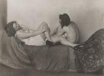 2 deels naakte vrouwen elkaar aankijkend op een bed