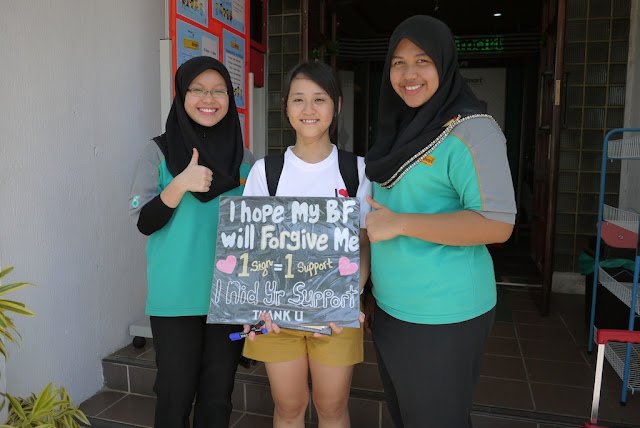 "Young woman holding a sign and standing next to two other young women. Sign reads "" I hope my BF will forgive me. 1 sign = 1 Support. I Nid Yr Support. Thank U."""