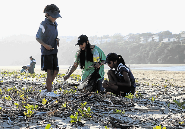 Rajeshree Govender, centre, and her two children, Uvesh, left, and Akiera, sift through the sand in search of nurdles and other plastic waste to fill up their eco-bricks, on Nahoon Beach