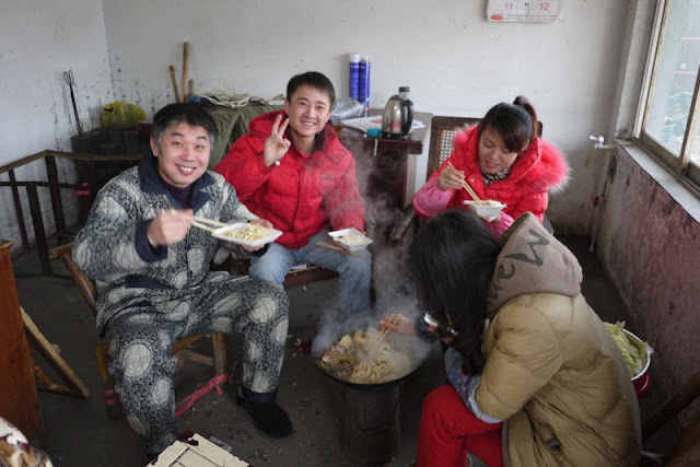 four people huddled around a hotpot