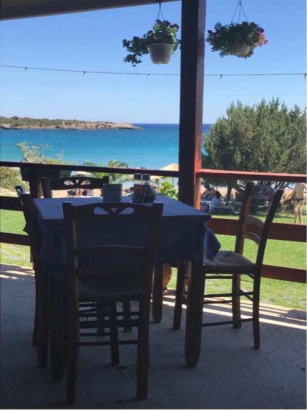 Et bord med stoler på en terrasse med utsikt mot en bukt.